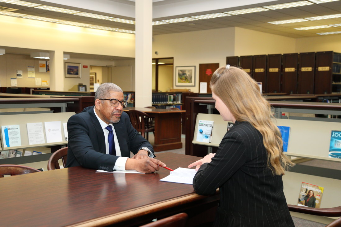 An african american man meets with a white woman at a table, going over a document. both are in business suits