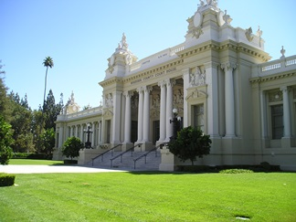 white courthouse building with green grass and blue sky