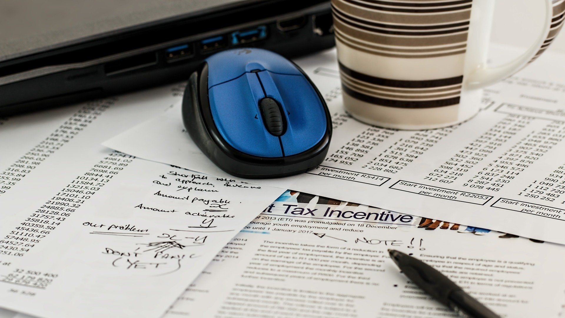 a blue computer mouse on top of papers with bottom of coffee mug visible